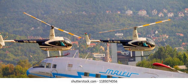 BUDAORS, HUNGARY - Sept 2 2018: Li-2 aircraft Ha LIX This aircraft. Two choppers fly by in the background.