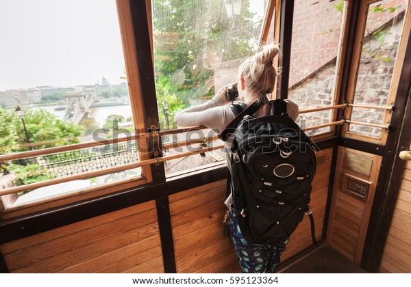 Budapest Castle Hill Funicular. Hungary. Female tourist photographing through glass trailer funicular Budapest panorama