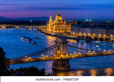 Budapest city at blue hour with illuminated Chain Bridge and Hungarian Parliament on Danube River, picturesque evening cityscape.