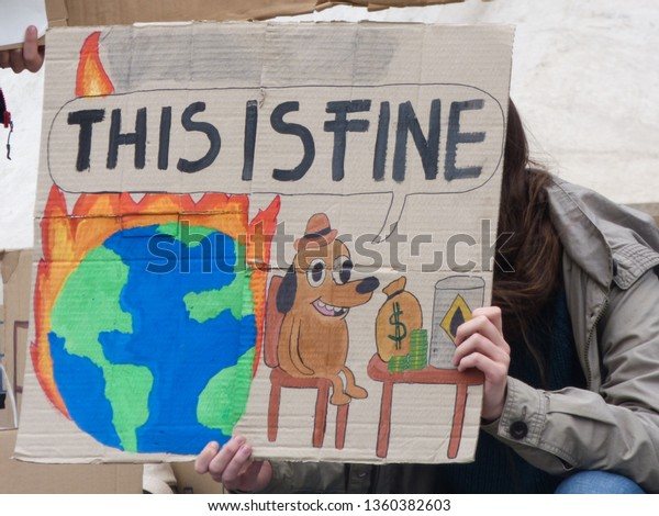 "Budapest, Hungary - 04.05.2019 Young protestor at a demonstration against climate change with the ""This is fine"" meme on it with a dog sitting on a place wich is burning or set in fire"