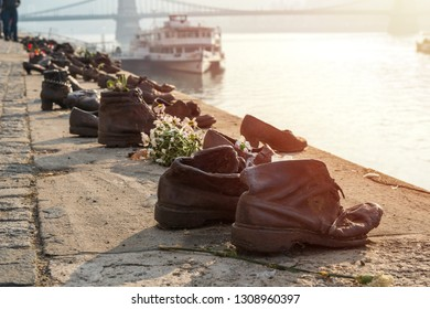 "Budapest, Hungary - 12.11.2018: ""Shoes on the Danube bank"" - Monument as a memorial of the victims of the Holocaust during world war II on the bank of the Danube at sunset in Budapest, Hungary."