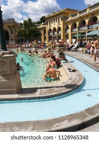 Budapest, Hungary - 1st. July. 2018: Thermal baths Széchenyi in open air with relaxing people on sunny day. Famous hungarian spa baths. Relax and leisure concept.