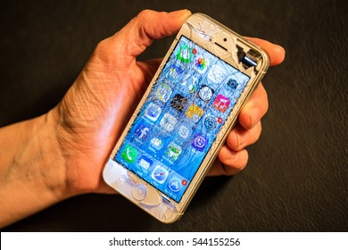 BUDAPEST, HUNGARY - 22 DEC 2016: Illustrative editorial photo of a broken smartphone with a cracked display in a woman hand on 22 December 2016 in Budapest Hungary