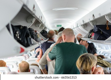Budapest, Hungary - 25th May, 2017. People are standing and sitting in an airplane cabin before disembarking.