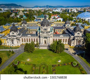 Budapest, Hungary - Aerial drone view of the famous Szechenyi Thermal Bath in City Park (Varosliget) on a sunny summer day with clear blue sky and green trees