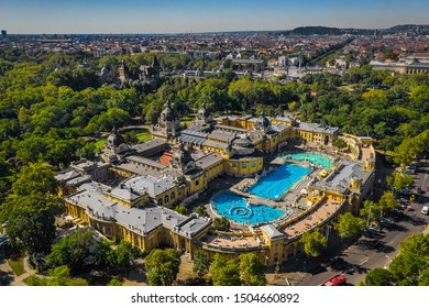 Budapest, Hungary - Aerial drone view of the famous Szechenyi Thermal Bath and Spa on a sunny summer day. Heroes' Square, Vajdahunyad Castle and Buda Hills at background.