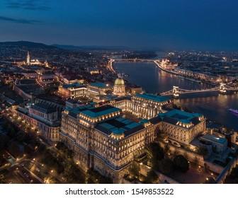 Budapest, Hungary - Aerial drone view of beautiful illuminated Buda Castle Royal Palace at dusk. Szechenyi Chain Bridge, Matthias church and Parliament of Hungary at background