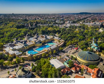 Budapest, Hungary - Aerial panoramic drone view of the famous Szechenyi Thermal Bath and Spa a sunny summer day. Heroes' Square, Budapest Circus, Budapest Zoo and Vajdahunyad Castle at background