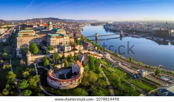 Budapest, Ungarn - Panoramasicht auf die Buda Burg mit Szechenyi Kettenbrücke, St. Stephan-Basilika, Ungarisches Parlament und Matthias-Kirche bei Sonnenaufgang mit blauem Himmel