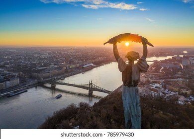 Budapest, Hungary - Aerial panoramic sunrise view at the Statue of Liberty with Liberty Bridge and sightseeing boat on River Danube taken from Gellert Hill