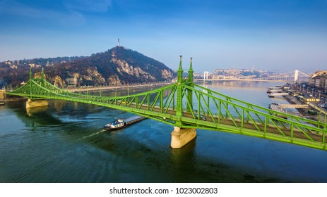 Budapest, Hungary - Aerial panoramic view of beautiful Liberty Bridge (Szabadsag Hid) with barge going on River Danube and Citadella, Statue of Liberty at background with clear blue sky