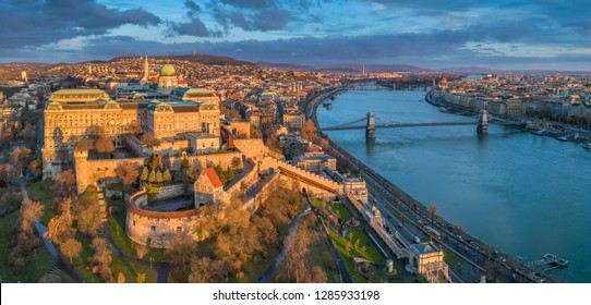 Budapest, Hungary - Aerial panoramic view of Buda Castle Royal Palace with Szechenyi Chain Bridge, Parliament and colourful clouds at sunrise