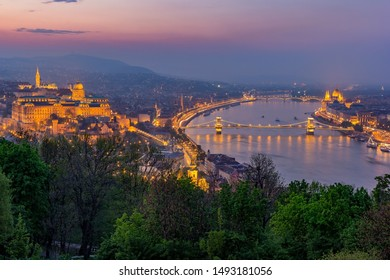 Budapest, Hungary - Aerial skyline view of Budapest at blue hour with illuminated Szechenyi Chain Bridge, Elisabeth Bridge, Citadel taken from above River Daube