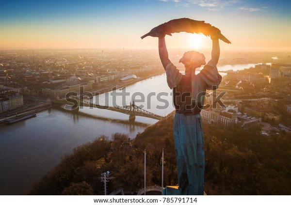 Budapest, Hungary - Aerial sunrise view at the Statue of Liberty with Liberty Bridge and River Danube at background taken from Gellert Hill