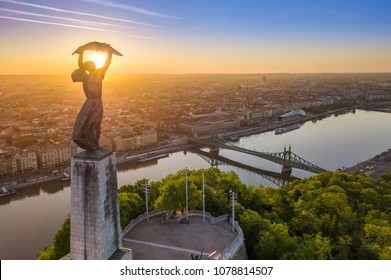 Budapest, Hungary - Aerial view of the beautiful Hungarian Statue of Liberty monument with Liberty Bridge and skyline of Budapest at sunrise with clear blue sky