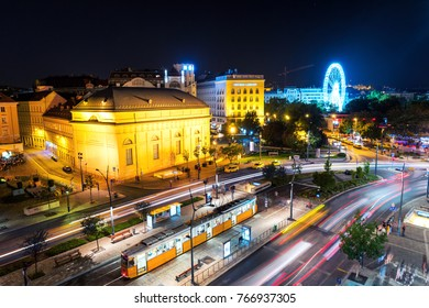 Budapest, Hungary. Aerial view of car and tram traffic at Small Boulevard in Budapest, Hungary. View of illuminated historical buildings, hotels, ferry wheel. Tram stop