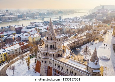 Budapest, Hungary - Aerial view of the snowy Fisherman's Bastion with Szechenyi Chain Bridge and St. Stephen's Basilica at background on a snowy winter morning
