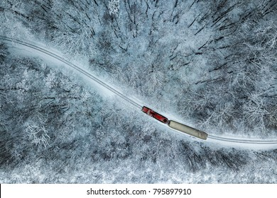 Budapest, Hungary - Aerial view of snowy forest with red train on a track at winter time, captured from above with a drone at Huvosvolgy