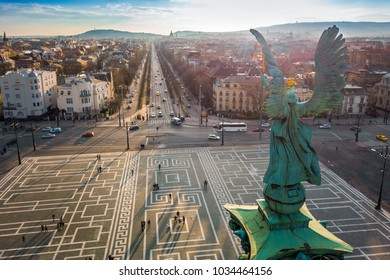Budapest, Hungary - Angel sculpture from behind on the top of Heroes' Square at sunset with Andrassy street and the skyline of Budapest at background