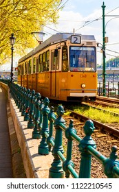 Budapest Hungary, April 18, 2018: Famous Number 2 Tram is passing by next to Duna-Korzo promenade with Buda castle complex on opposite shore of Danube river in Budapest.  Called The Site Seeing Tram.