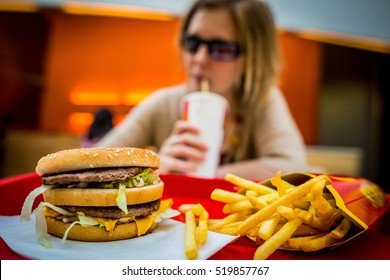 BUDAPEST, HUNGARY, April, 2013: Young woman eating a Big Mac hamburger menu in a McDonald's restaurant. Illustrative editorial.