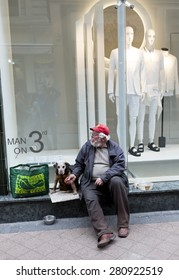 Budapest, Hungary - April 30, 2015: An old man is begging in front of a fashion shop in a main street in Budapest, Hungary.