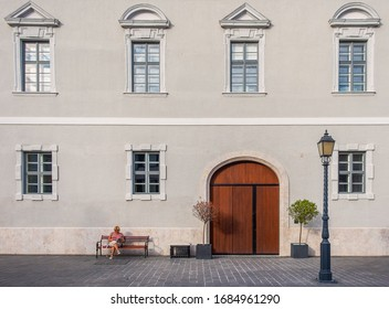 Budapest, Hungary, Aug 2019, woman sitting on a bench and reading by a building in the Buda Castle District