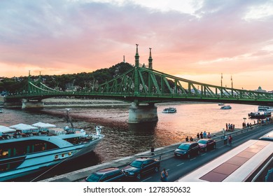 BUDAPEST, HUNGARY - AUGUST 10, 2018: Liberty Bridge at sunset. Famous green bridge is a historical monument and popular for tourist visits. A few boats are swimming on the Danube river. Panorama