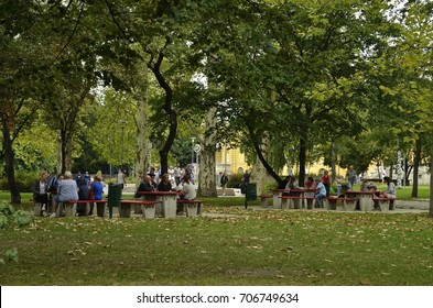 Budapest, Hungary - August 13, 2017: Locals sitting at the public dining area in the City Park, near the Szechenyi bath among the autumn trees