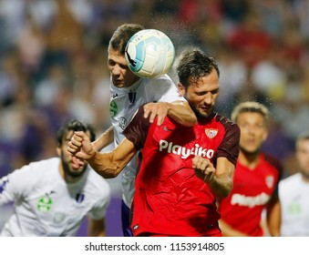 BUDAPEST, HUNGARY - AUGUST 2, 2018: (l-r) Benjamin Balazs battles for the ball in the air with Franco Vazquez during Ujpest FC v Sevilla FC UEFA EL match at Ferenc Szusza Stadium.