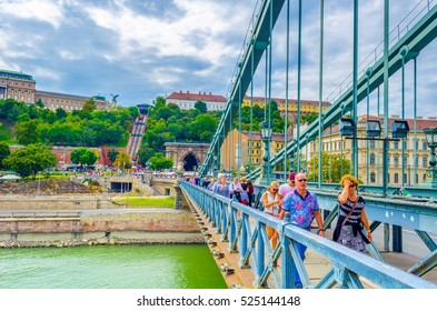 BUDAPEST, HUNGARY, AUGUST 20, 2015: crowds of people are crossing danube through szechenyi lanchid bridge in budapest.