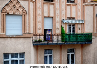 Budapest, Hungary - August 2015: Old woman looks at the street from her balcony, Budapest