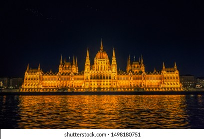 Budapest / Hungary - August 29 2019: Hungarian Parliament building and Danube River in the   Budapest city at night. A sample of neo-gothic architecture, Budapest's tourist attraction