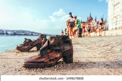 Budapest / Hungary - August 29 2019: Tourists looking at the old metal rusty shoes on the parapet of the Danube river embankment in Budapest, Hungary. Monument to the victims of Nazi repression