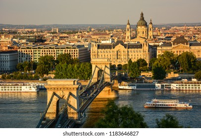 Budapest / Hungary — August 3, 2013: a sunset view of the Danube in Budapest with the Chain Bridge, a famous bridge connecting Buda and Pest districts of the city, and St Stephen's Basilica
