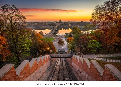 Budapest, Hungary - Autumn in Budapest. The Castle Hill Funicular (Budavári Siklo) with the Szechenyi Chain Bridge and St. Stephen's Basilica at sunrise with autumn foliage