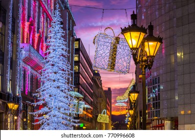 Budapest, Hungary - Beautiful shopping street scene with lamp post, glowing Christmas tree and lights and decorations and colorful sunset sky in central Budapest
