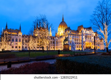 Budapest, Hungary - Dec 14 2018: Tourists enjoy the Christmas lights at the Parliament House in Budapest, Hungary. This traditional Christmas fair attracts over a million visitors each year.