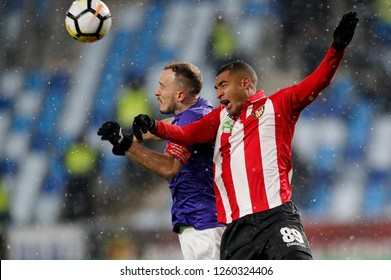 BUDAPEST, HUNGARY - DECEMBER 15, 2018: (l-r) Robert Litauszki of Ujpest FC battles for the ball in the air with David N'Gog of Honved during Budapest Honved v Ujpest FC match at Hidegkuti Stadium.