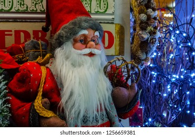 BUDAPEST, HUNGARY - DECEMBER 20, 2017: Christmas toy Santa Claus for sale in the store on the background of Christmas wreaths and lights from led lamps.