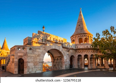 Budapest, Hungary - Entrance and tower of Fisherman's Bastion (Halaszbastya) on a golden autumn sunrise with Parliament of Hungary and Margaret Bridge at the background and clear blue sky