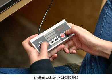 BUDAPEST, HUNGARY - FEBRUARY 17, 2018: Playing the classic Nintendo NES console from the 80s, controller closeup