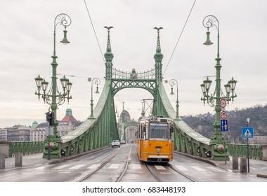 BUDAPEST, HUNGARY - FEBRUARY 21, 2016: Liberty Bridge or Freedom Bridge and yellow train in Budapest, Hungary.
