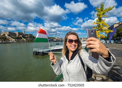 Budapest, Hungary - Happy tourist holding Hungarian national flag and taking slefie with smartphone at the Buda Castle Royal Palace. Excited girl sightseeing travel by River Danube on a summer day