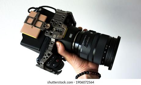Budapest, Hungary - January 31, 2020: man holding his Black Magic camera, with sigma ART 24-70 lens.