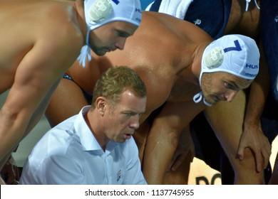 Budapest, Hungary - Jul 25, 2017. MARCZ Tamas, head coach of Hungary Men Waterpolo team talking to the players (TOROK Bela, DECKER Adam). FINA Waterpolo World Championship.