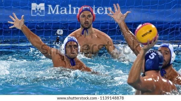 Budapest, Hungary - Jul 27, 2017. PONTIKEAS Kyriakos (7) and FLEGKAS Konstantinos (1) defend against VAMOS Marton (5). FINA Waterpolo World Championship, Semifinal.