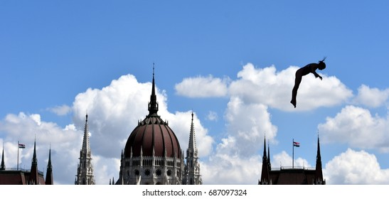 Budapest, Hungary - Jul 28, 2017. Woman dives from the 20 metre platform during the semi-final day of women`s High Diving at the FINA World Championships. The Hungarian Parliament in the background.