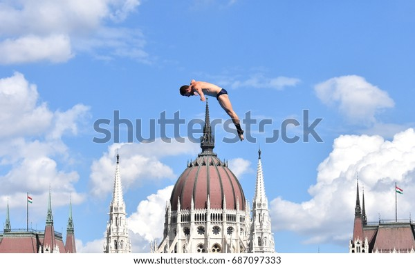 Budapest, Hungary - Jul 28, 2017. Man dives from the 27 metre platform during the semi-final day of men`s High Diving at the FINA World Championships. The Hungarian Parliament  in the background.