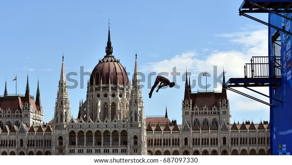 Budapest, Hungary - Jul 30, 2017. Blake Aldridge dives from the 27 metre platform during the final day of men`s High Diving at the FINA World Championships. Hungarian Parliament in the background.